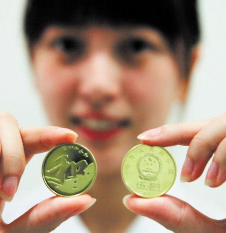 """银行工作人员展示去年9月央行发行的5元""""和""""字币。 新华社发"""